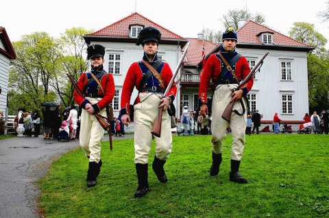 EIDSVOLL 1814: Soldater fra Søndenfieldske Infanteriregiment Onsøske Compagnie patruljerer foran Eidsvollsbygningen. Fra venstre Ola Johnsgaard Moen, Ole Johan Myhre og Magne Bondkall.