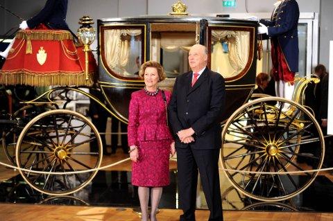 Kong Harald  og Dronning Sonja fikk overrakt regjeringens gave til sine 75-årsdager - den første av seks kongelige utstillinger. Her står de foran den staselige kroningsvognen fra 1906.