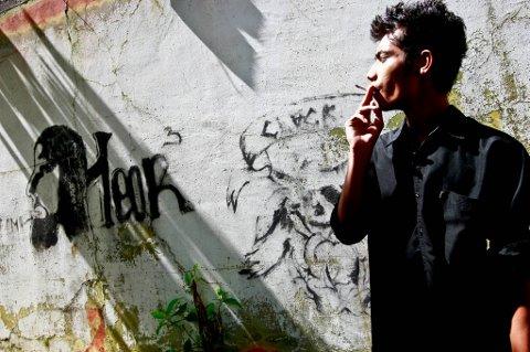 En ung mann røyker en sigarett på gata i Øst-Timor. Det er gått 50 år siden britiske leger først advarte om skadevirkningene av tobakk. I løpet av disse årene har mange mennesker verden over stumpet røyken, mens andre fortsetter. I Storbritannia, som var først ute med advarslene, er en femdel av befolkningen fortsatt røykere. Svært mange av disse kommer til å lide tobakksdøden.