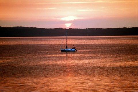 Slår spådommene til, blir det mindre vind i Danmark i sommer. Bildet viser en seilbåt i solnedgang utenfor Ebeltoft.