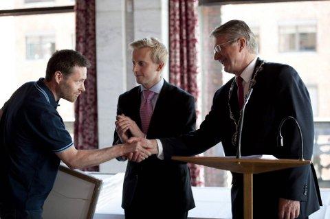 Øyafestivalens daglige leder Stein Arne Blomseth (t.v.) tar imot prisen fra Oslo-ordfører Fabian Stang og leder i utdanningskomiteen, Øystein Sundelin.