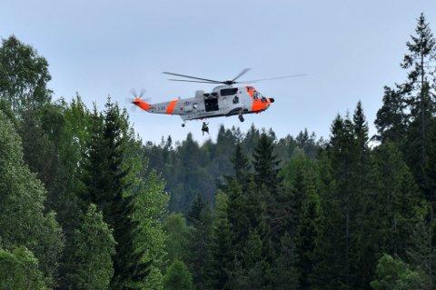 REDDET: Den 17 år gamle savnende jenta blir her heist opp av forsvarets Sea King-helikopter i sørenden av Åmodtdammen i Rælingen. FOTO: RAYMOND BOE