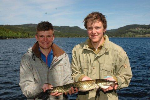 FISKEKOMPISER: Magnus Reinsby Gihle (t.v.) og Vegard Vingebakken er fiskekompiser. Når den ene har fisk på kroken, hjelper den andre til med håven. Da er det rett og rimelig å vise fram fangsten sammen også.