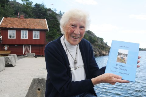 Aslaug Eirheim er klar med boka «Borøyvandringer - gjennom ny og gammel tid». Hun og ektemannen Odd har bostedsadresse i Bærum, men tilbringer store deler av året i  det røde huset (i bakgrunnen) på bryggekanten i Sandvika.