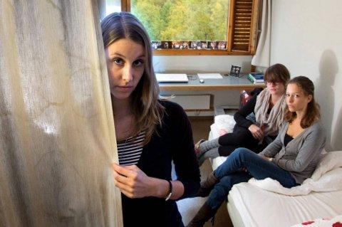Lena Pepenfoss viser frem det skitne forhenget som møtte henne da hun flyttet inn i Studentsamskipnadens hybel i Åsgårdveien. Både hun, Lisette Waanders (til høyre) og Nora Wagner (i midten) har mugg i hyblene.