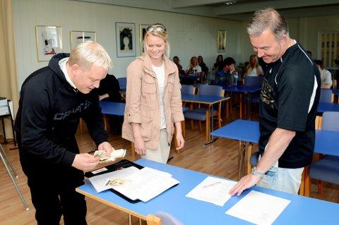 Roland Nilsen fra IMS blar opp restbeløpet bedriften lovet russen i Risør om de holdt seg unna ulovlige rusmidler. Her er det Tuva Røysland som mottar penger til russebilen hun er med på, mens Bjørn Kolmannskog fra politiet bivåner det hele.