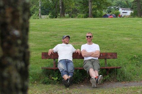 FOR 13. GANG: Tor Baklund (t.v.) og Trond Tertnes sittende ved sentrumsstranda Hagemann, basen til årets versjon av RockArt. Duoen er del av gjengen som sørger for at Holmestrand har en unik rock- og kunstfestival for 13. år på rad.