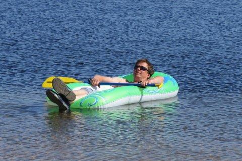 EN FJERN DRØM: Mens regnet høljet ned og vinden ulte over tundraen, var livet ved Baktus Bay allerede blitt en fjern drøm ... her ser vi Jan Maurits i lagets medbragte gummibåt (hva nå enn den gjør på tundraen) mens han nyter livet i den alvorlig utfordrende solsteiken.