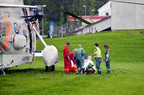 En skadd person blir her fraktet over i Sivilforsvarets helikopter fra ambulansen, på Voss. Totalt er 73 personer sendt til sykehus etter at et vogntog tok fyr i Gudvangatunnelen.