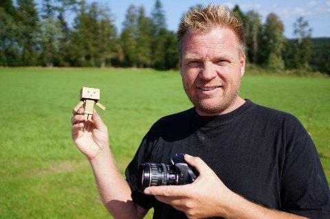 Tord Nilsen viser frem pappfiguren som beveger seg rundt på fine steder og arrangementer i Halden.