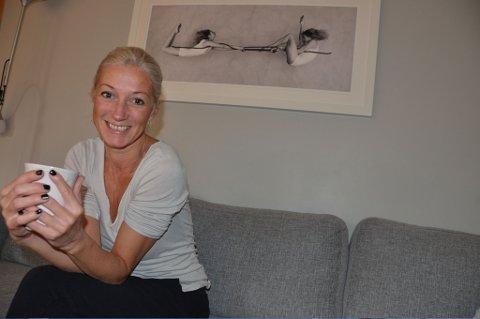 Klara Szalai Ørbæk hjemme i Larvik. Bak henne henger et fotografi fra et av høydepunktene i hennes egen karriere.