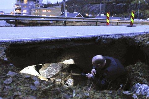 Gravde ut. Like etter at skolebussene hadde passert Djupvika på Ørnes, måtte fylkesveien stenges fordi flomvann hadde gravd ut veilegemet. Her inspiserer brannmann Odd Arne Berbusmel det digre hullet under asfalten.