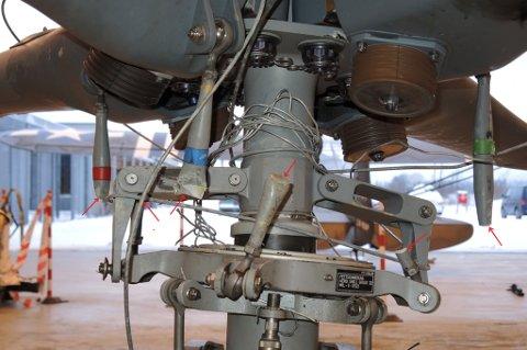 Hovedrotorhodet på helikopteret. Bruddene på tre av fire synlige kontrollstag er merket med røde piler. Det fjerde staget er skjult bak rotormasten. Deler av høyspentledningen sees kveilet rundt rotormasten.