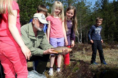 NÆRKONTAKT MED NATUREN: Marikken (7), Tonetta (8) og Nicolay (8) følger spent med når Stein Svenneby i Lørenskog jakt- og fiskeforening (LJFF) slipper en treårig halvkilosørret uti vannet. Foto: Torstein Davidsen