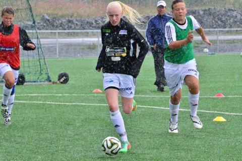 Tonje Kopperud Olsen (Høland IL) og Anders Nordby Skrefsrud (Høland (IL)  kjemper om ballen mens regnet strømmer ned. Til venstre kommer Petter Tøien (Søndre Høland IUL) i fullt driv.