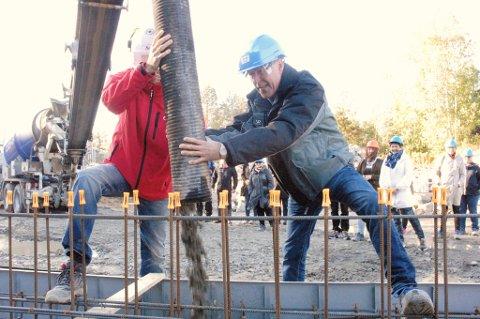Ordfører John Harry Skoglund sender den første sementen ned i forskalingen og byggingen av Fets største barnehage, Tienbråten, er i gang. Anleggsleder Kjell Arne Gaard i Seby AS til venstre.
