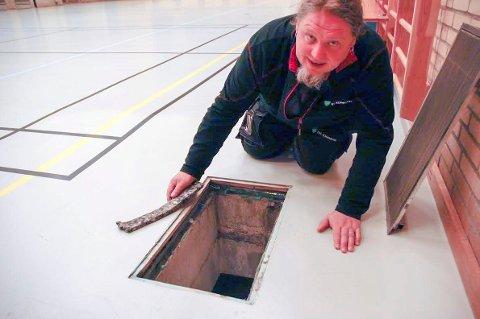 Inspiserer: Vaktmester Dannis Grepperud viser fram en bit av underlaget som har trukket til seg vannet. Foto: Per chr. utsigt