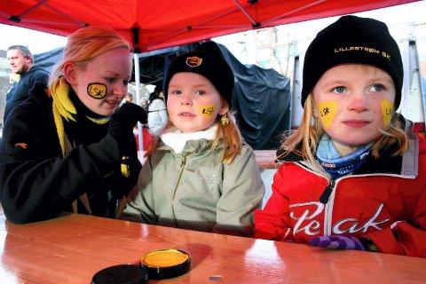 DAGEN FØR DAGEN: Camilla Scheflo (18) i Kanarifansen maler hjerter i LSK-farger på kinnene til Mathea Kjelvik Kristiansen (5) (t.v.) og Elina Kjelvik (4) (t.h.). ? Vi er her for å feire fugla, sier Mathea.