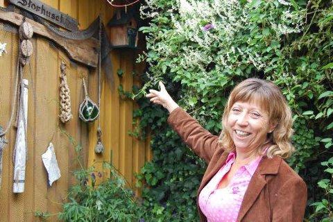 Flere beboere: Anne Norløff setter pris på selskap av dyrene og fiskene i hagen. Her peker hun på en liten fuglekasse som var hjemmet til et blåmeispar.