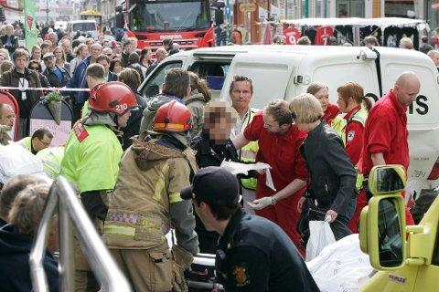 MANGE VITNER: Dødsulykken midt i Storgata vakte naturlig nok stor oppsikt midt på lyse ettermiddagen i Tromsø. Her får en av de lettere skadde hjelp av ambulansepersonell.