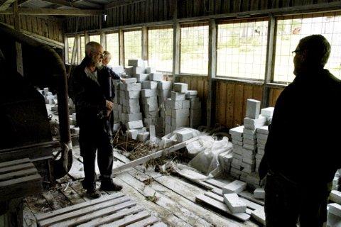 RESTENE:Rester av siste produksjon av foringsstein til ovner ligger fortsatt i saghuset på Åsen, viser Kjell Voldheim. Foto: Leif Øverland