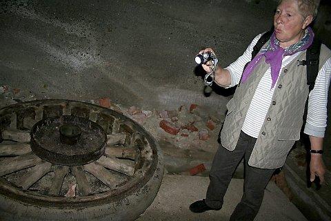 LOMMEKJENT: Solveig Pedersen-Titternes har lekt mye i de gamle bunkerene som barn og siden hun også hadde medbrakt hodelykt falt det seg naturlig at hun var guide under ekskursjonen på Heia. Her ved en av hjulene som har tilhørt en av tyskernes kanoner.