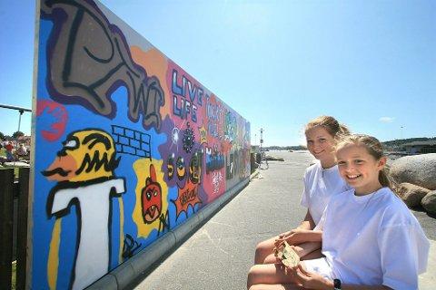 12 meter graffiti: Gøy å prøve seg på ordentlig graffiti, sier Andrine Larsgård (14) (t.v.) og Anine Ringdal (11), som begge har vært med og dekorert veggen som er utstilt i Indre havn. (Foto: Sigrid Ringnes)