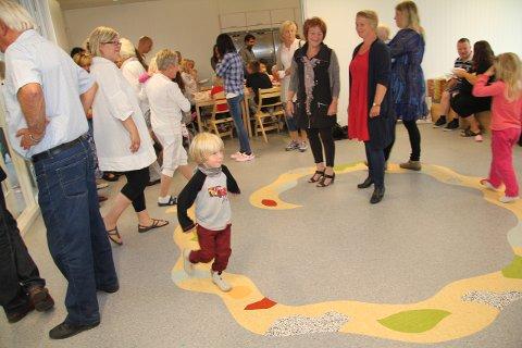 Odin Haraldsønn fant fort ut at den fargerike slangen på gulvet i fellesrommet var en fin vei og løp rundt og rundt mens Reidun Bollerud fra Kulturseksjonen og kunstneren Sofie Nordin fulgte med.