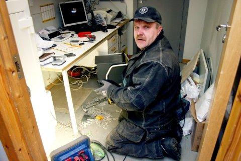 REPARASJON: Aivars Miezis fra Kvikk Service AS var mandag formiddag i gang med å reparere hullet under kontorbordet på Prix Olderskog. (Foto: Christopher Engås)
