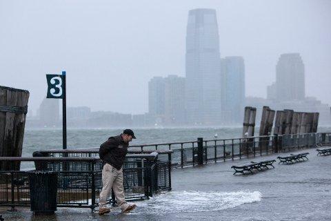 En mann tusler rundt ved elven nederst på Manhattan i New York mens uværet «Sandy» nærmer seg mandag.