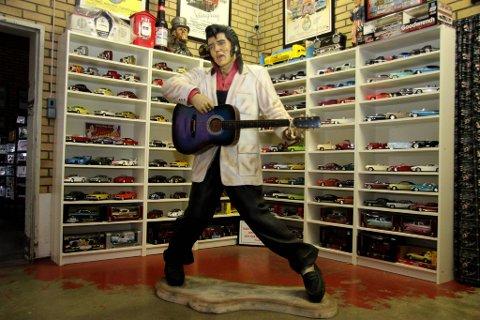 Velkommen: Elvis Presley hilser velkommen. Bak ham står hundrevis av amerikanske småbiler.
