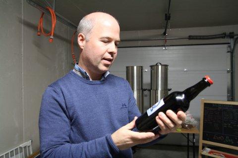 """Stian Sjursen Takle har brygga mange ølsortar i år. Her står han med kveitebrygget """"Farsund"""", laga i mai i år."""