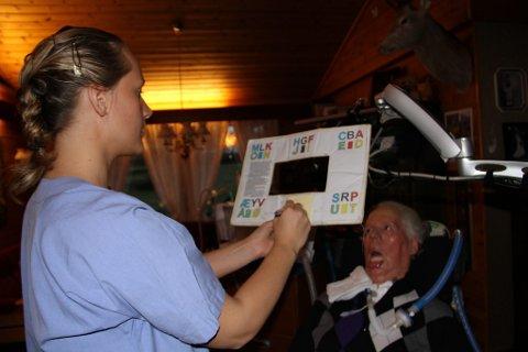 AKTIV KOMMUNIKASJON: Med  hjelp av augene og bokstavtavla, og Michelle som er ein kløpper i bruken av denne, kommuniserer Magne med nh sin utsende. Det går i eit imponerande tempo.