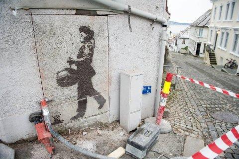Huseier har skåret i muren rundt kunstverket. Nå skal det bort.