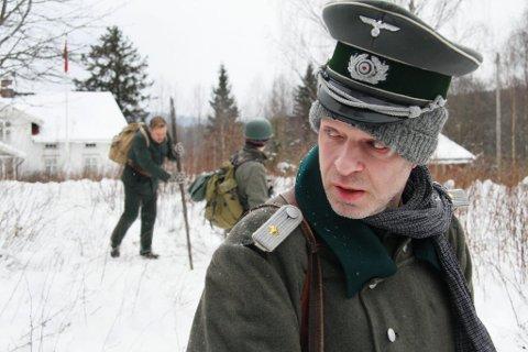 PRØVER: Scenen gås gjennom før opptak. Da kamera gikk hadde Mats Reinhardt fjernet strikkelua under uniformslua.
