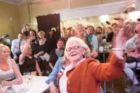 VIFTER MED SKOENE: Leonora T. Johansen og andre blant publikum vifter med skoen sin og synger «sko» i refreng til en sang som handler om sko.