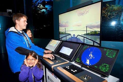 HAVBRUKSUTSTILLING: Uscha, Kjell-Magne og Mira (7) Paasche tester ut simulatoren som er utstilt i museumsavdelingen med navn «Landet med det store havet utenfor».