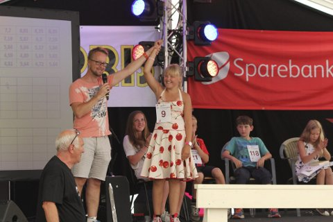 Sara Lutro (13) frå Urheim ved Lofthus vann juniorklassen for andre gong, og viser at ho er eit spyttetalent å rekne med for framtida. Her vert ho gratulert av konferansier Sigurd Sollien.