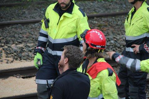 Brannvesenet og politi er på plass og sjekker togskinnene.