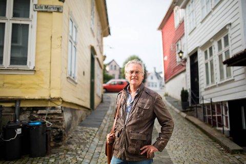 Forfatter Gunnar Staalesen har Amalie Skram som ett av sine litterære forbilder, og vet mye om hennes liv. Her står han utenfor en av husene hvor hun bodde, i Cort Piilsmauet 1 (til venstre). I helgen er han aktuell som dramatiker med premiere på «Hellemyrsfolket» på DNS.