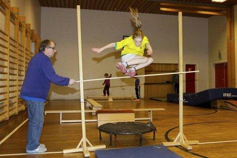 Innendørstrening på Mosjøen skole er Eirin Kvandal vant med. Her får hun hjelp av pappa Asle til å holde lista høyt. Styrketrening, lek og ikke minst Vidars hinderløype står på programmet hver tirsdag hele høsten.  Foto: Per Vikan