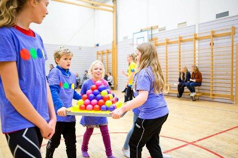 Elevene deles inn i grupper bak hvert av brettene. Én og én løper de fra hvert av lagene for å hente baller.