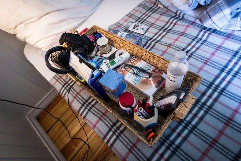 Brettet er livet: Ved siden av seg i senga har Anniken dette brettet med blant annet bok, høretelefoner, Pringles og vitaminbjørner. Ved siden av senga står det alltid ei rød plastbøtte.