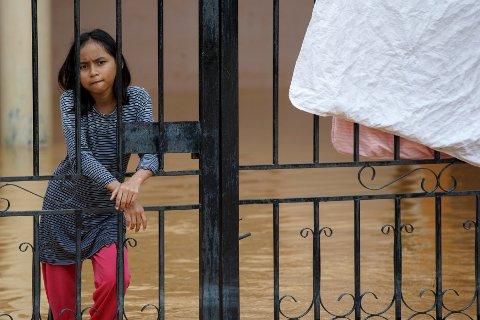 En jente ser utover Kota Bharu I Kelantan 29. desember. Oversvømmelsen har tatt livet av ti personer og tvunget nærmere 160.000 bort fra hjemmene sine.