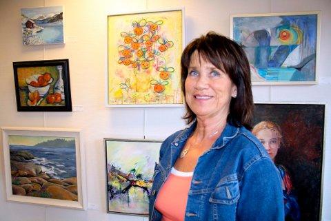 Trine  Narten Enkerud er debutant på Bamble Malerklubbs sommerutstilling. Hun stiller blant annet ut det gule maleriet «Blomsterkor» som henger på veggen bak henne her.