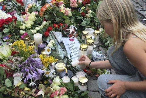 Ei jente tenner lys for å minnes de mange døde.