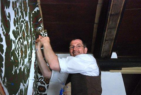 Rett på veggen: Peter Eggert syr det veluriserte veggkledet sammen rett på veggen, med en spesiell buet nål og lintråd. (Foto: Kjersti Bache)