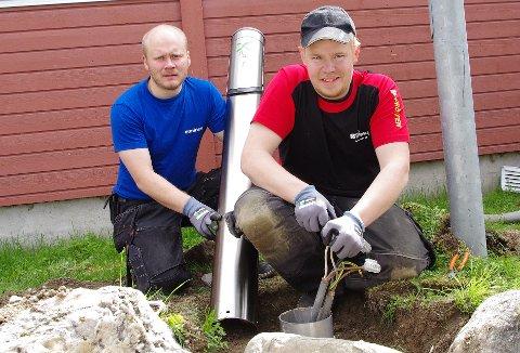 Kristian Berg (til venstre) og Morten Ryen roter i jorda og er i ferd med lage ladestasjoner for el-biler ved sjukehuset på Tynset.