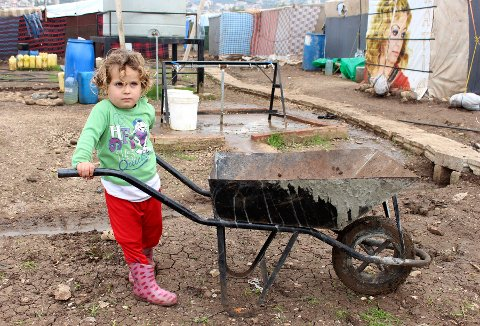 En syrisk jente leker utenfor teltene i en flyktningleir i Libanon.