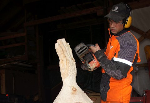 Motorsagkunstnar Arne Askeland formar ein trestokk til ei hand.